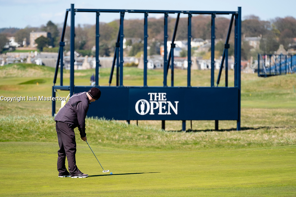 Golfer putting on green in front of scoreboard under construction at Carnoustie Golf Links in Carnoustie, Angus, Scotland, UK. Carnoustie is venue for the 147th Open Championship in 2018.