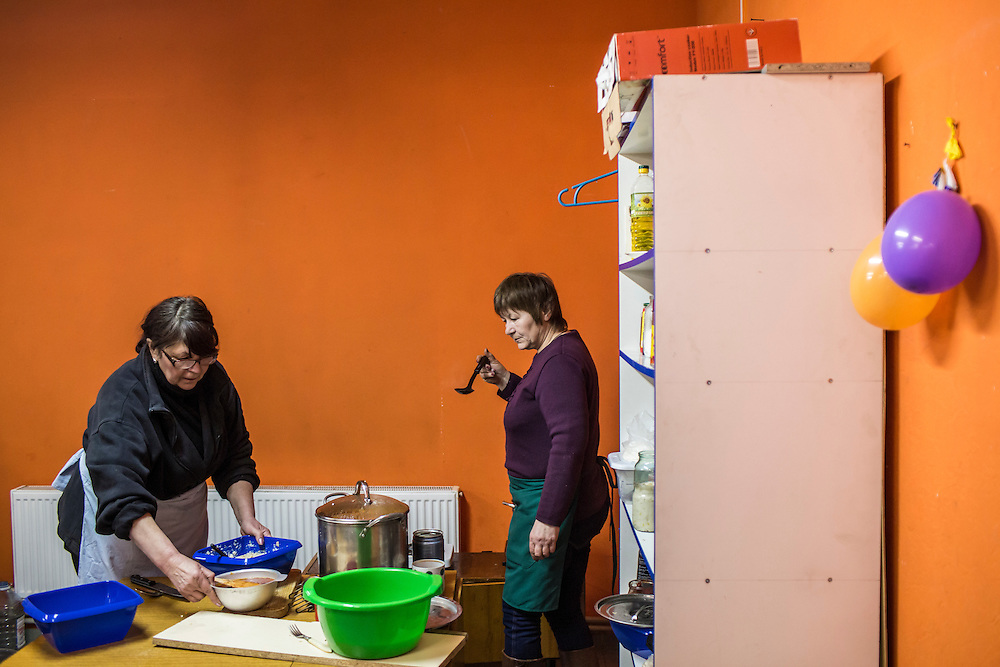 MARIINKA, UKRAINE - FEBRUARY 20, 2016:  Tatyana Grintsova, left, and Anna Manayenkova prepare food for visitors and members of the congregation at the Church of the Transfiguration in Mariinka, Ukraine. The Donetsk suburb has been the scene of some of the heaviest fighting recently between Ukrainian forces and pro-Russian rebels. CREDIT: Brendan Hoffman for The New York Times