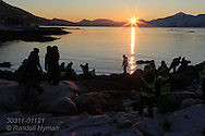 School groups stand at Telegrafbukta at south end of Tromsoya island on January 21st watching the return of the sun after two months without sunrise ; Tromso, Norway.