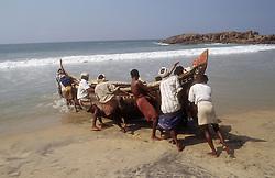 Men pushing fishing boat into the sea at Kovalam beach; Kerala; India,