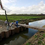 Nederland Zevenhuizen 12 november 2008 20081112 Foto: David Rozing ..Serie Zuidplaspolder, bouwvakkers storten cement tijdens aanleg nieuwe randweg voor Zevenhuizen, welke op dit punt een brede watergang passeert. Dit is het allereerste infrastructurele project dat wordt uitgevoerd van de plannen voor de Zuidplaspolder, pas als deze randweg af is  zullen de andere projecten volgen.  ..De Zuidplaspolder is de laagste plek in Nederland en Europa, het laagste punt in de polder meet 6,76 meter onder NAP. Omdat het gebied zo laaggelegen is zijn  plannen voor deze polder omstreden/ is er een felle discussie over.  .De Zuidplaspolder is in de Nota Ruimte aangewezen als één van de grote ontwikkelingslocaties in Nederland.  Er moeten 15.000 tot 30.000 nieuwe woningen komen, 150 tot 250 ha bedrijventerreinen, mogelijk 200 ha extra glastuinbouw en waterberging. Om deze verstedelijking mogelijk te maken wordt de grens van het Groene Hart aangepast. Duurzaamheid is een belangrijk onderdeel bij de planning en uitvoering..Het gebied is aangewezen als studielocatie voor stadsuitbreiding. Tegenstanders geven aan dat gezien de diepte van de polder waterproblematiek zich onafwendbaar zal gaan voordoen. Voorstanders geven aan dat met aanpassingen in het watersysteem en goede planning zoals wonen, werken, recreëren gepland op plekken waar dat gezien het water en de bodem het meest gunstig het een veilige omgeving zal zijn. ..Foto: David Rozing