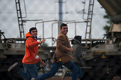 **Images taken on the evening of the 11th of August** © London News Pictures. 11/08/2015. Calais, France. A group of young migrants taunt transport police by waving their hands in the air and running past them on the Eurotunnel tracks. Photo credit: Ben Cawthra/LNP