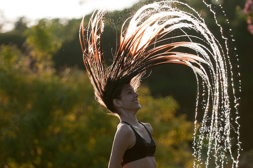 13 year old girl swinging her wet hair, Kauai, Hawaii