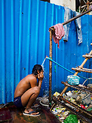 "12 FEBRUARY 2019 - SIHANOUKVILLE, CAMBODIA:  A Cambodian construction worker bathes at a public water spigot outside the the Blue Bay casino and resort development under construction in Sihanoukville. There are about 50 Chinese casinos and resort hotels either open or under construction in Sihanoukville. The casinos are changing the city, once a sleepy port on Southeast Asia's ""backpacker trail"" into a booming city. The change is coming with a cost though. Many Cambodian residents of Sihanoukville  have lost their homes to make way for the casinos and the jobs are going to Chinese workers, brought in to build casinos and work in the casinos.     PHOTO BY JACK KURTZ"