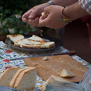 Chef prepares to apply garlic to toasted bread as he conducts a cooking class for tourists staying at the Villa Rosa agriturisimo, Panzano in Chianti, Italy - no release available<br />