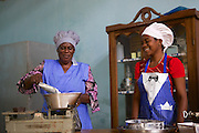 Joyce Marwa (left) weighing flour on some scales.<br /> <br /> Joyce set up and now runs a bakery that bakes bread and cakes. She also processes nutritious flour (a mix of 5 grains)<br /> <br /> She attended MKUBWA enterprise training run by the Tanzania Gatsby Trust in partnership with The Cherie Blair Foundation for Women.