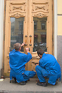 Workers restoring an old door<br /> St. Petersburg, Russia