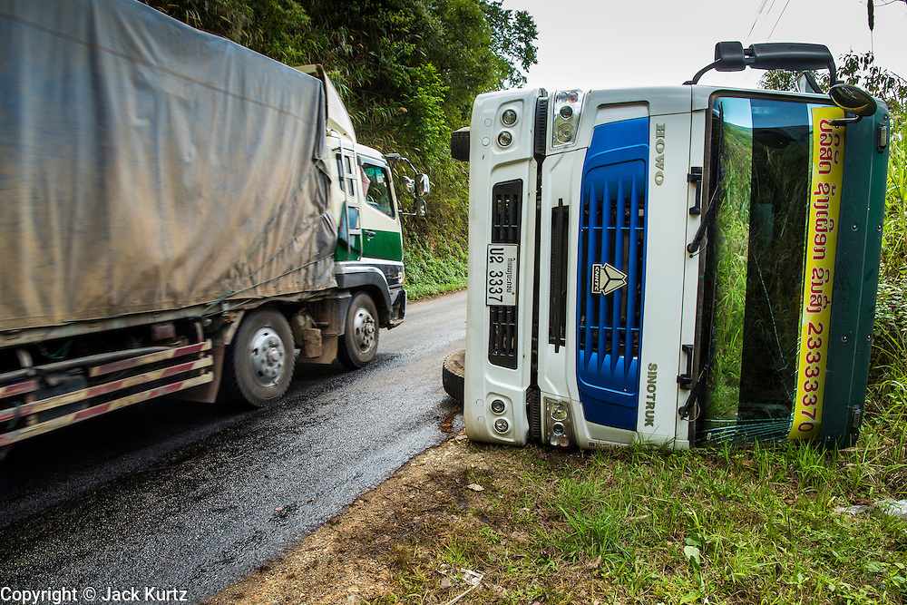 10 MARCH 2013 - ALONG HIGHWAY 13, LAOS: A truck hauling freight from China passes an overturned truck on Highway 13. The paving of Highway 13 from Vientiane to near the Chinese border has changed the way of life in rural Laos. Villagers near Luang Prabang used to have to take unreliable boats that took three hours round trip to get from the homes to the tourist center of Luang Prabang, now they take a 40 minute round trip bus ride. North of Luang Prabang, paving the highway has been an opportunity for China to use Laos as a transshipping point. Chinese merchandise now goes through Laos to Thailand where it's put on Thai trains and taken to the deep water port east of Bangkok. The Chinese have also expanded their economic empire into Laos. Chinese hotels and businesses are common in northern Laos and in some cities, like Oudomxay, are now up to 40% percent. As the roads are paved, more people move away from their traditional homes in the mountains of Laos and crowd the side of the road living off tourists' and truck drivers.    PHOTO BY JACK KURTZ