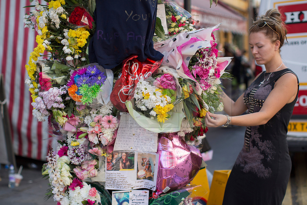 © licensed to London News Pictures. London, UK 26/08/2013. Friends of Sabrina Moss paying their respects at a floral memorial to nursery teacher Sabrina Moss who was shot dead in Kilburn while out celebrating her 24th birthday. Photo credit: Tolga Akmen/LNP