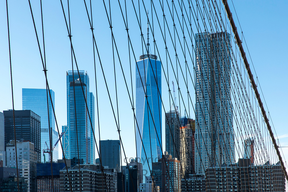 Skyscrapers of Manhattan viewed through wire supports and cables of Brooklyn Bridge, New York City