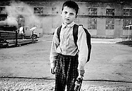 A Chechen refugee boy collects bottles in an abandoned cement factory outside the refugee camp of Bart on the outskirts of Karabulak in Ingushetia.  July 2002.