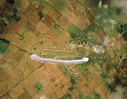 Looking down vertically upon the Hawk jet aicraft of the elite 'Red Arrows', Britain's prestigious Royal Air Force aerobatic team, the team loop over agricultural countryside during an In-Season Practice (ISP) training flight near their base at RAF Scampton. Roman Ermine Street road is a diagonal line through the centre, dissecting wisps of organic white smoke left hanging in the air. Reforming in front of a local crowd at the airfield they work through a 25-minute series of display manoeuvres that are loved by thousands at summer air shows. Freshly-ploughed English fields with properties, roads, hedgerows plus former nuclear silos are seen below. After some time off, spare days like this are used to hone their manual aerobatic and piloting skills before re-joining the air show circuit. Since 1965 they've flown over 4,000 shows in 52 countries.   .