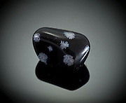 Cutout of a snowflake obsidian gemstone on black background