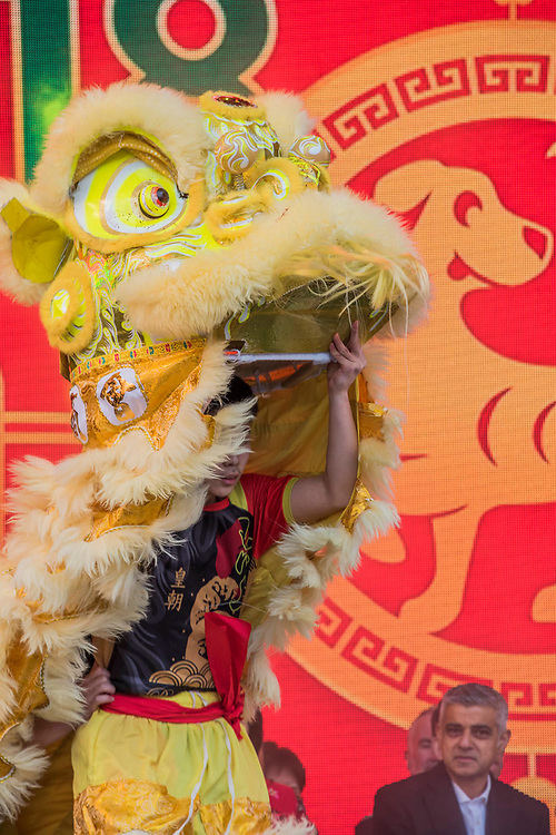 Sadiq Khan, Mayor of London, on stage with Chinese Dignitaries as the Lion Dance begins - Chinese New Year Celebrations in London 2018 marking the arrival of the Year of the Dog. The Event started with a Grand Parade from the North East side of the Trafalgar Square and finishing in Chinatown at Shaftesbury Avenue. It was organised by London Chinatown Chinese Association and is supported by The Mayor of London and Westminster City Council.