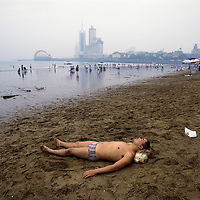 Saturday morning on a downtown beach facing onto the Yellow Sea during the city's annual beer festival...From China [sur]real © Mark Henley..