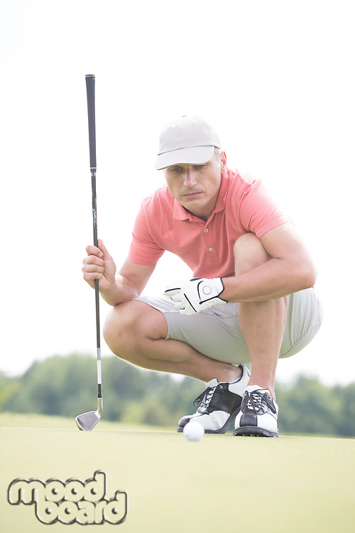 Middle-aged man aiming ball while crouching on golf course