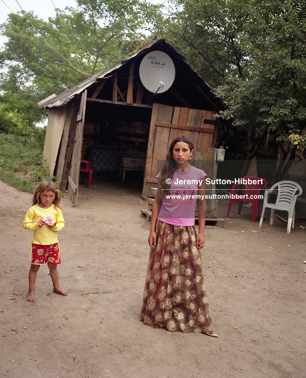 """13 year old Mia (on right), stands in front of a shed with a cable Television satellite dish, in the """"old"""" part of the village of Sintesti, in Romania, early August 2006. The old part of the village houses the poorer families within the camp who have not yet earned enough money to move down nearer to the main road, and to build a new home. The Kalderari roma of Sintesti are by tradition metal workers, originally making alcohol stills, pots and pans, but now dealing in scrap metal. The large profits from their business have enabled them to build large houses in the village of Sintesti, 20km from Bucharest, and to invest in fast, Western brand name cars such as BMW's, Mercedes and Porsche."""