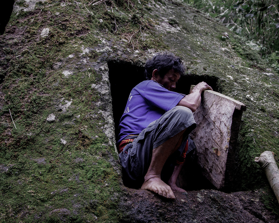 A family member covers the opening of a  a hole carved inside a cliff where the remains of his relatives were put to rest.<br />