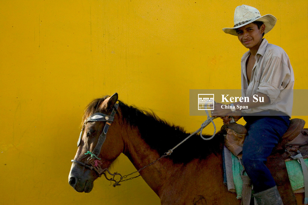 Man on horseback in front of yellow wall, Honduras
