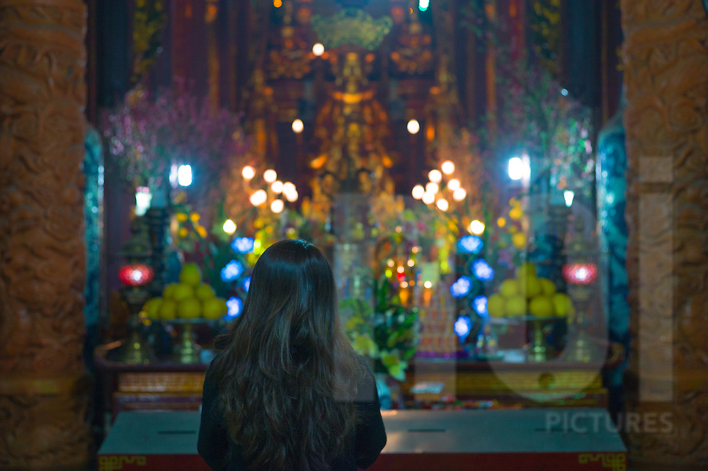 A Vietnamese woman prays in Quan Su Pagoda on Tet eve, Hanoi, Vietnam, Southeast Asia, 2013