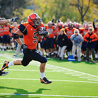 10/30/10 - Gettysburg, PA: Gettysburg wing back Charles Curcio (5) rushes past Susquehanna line backer Mitch Phillips (56) with a go-ahead 4 yard touchdown with 1:40 left in the game. The Bullet's 61-50 win consisted of a game total 1,162 yards, a 34 point comeback in the final 18 minutes, a Centennial Conference record for combined points, and a first quarter brawl in their first match since 1922!<br />