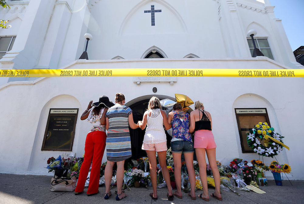 A group of women pray together at a make-shift memorial on the sidewalk in front of the Emanuel AME Church, Thursday, June 18, 2015 in Charleston, S.C. The chief of police of Charleston, Greg Mullen, called the shooting at the church Wednesday a hate crime, and an official with the Justice Department said that a federal investigation had been started and that it could be conducted in cooperation with the state inquiry. (AP Photo/Stephen B. Morton)