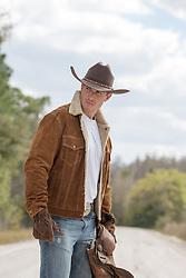 cowboy in a sheepskin suede jacket carrying a saddle on a dirt road