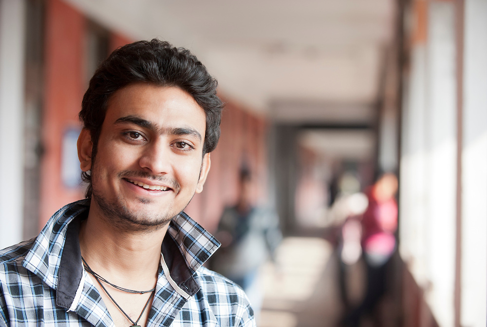 Young Indian male student smiling cheerfully on university campus
