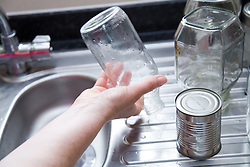 Woman washing out jars and tins for recycling,
