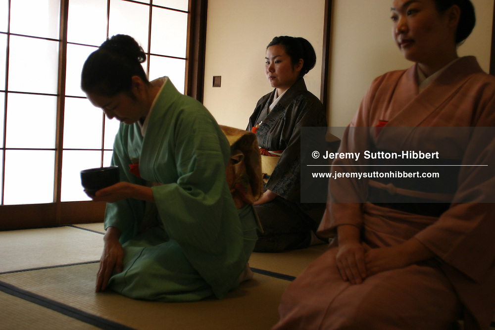 """A student holds a cup, whilst practicing her 'tea ceremony' skills. The art of the """"tea ceremony', as practiced at the Chadou-Kaikan, a school to teach the traditional tea ceremony skills. Pupils attend to learn the tea making skills, and also about Japanese history, tradition and manners. Takadanobaba, Tokyo, Japan"""