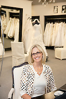 Portrait of a happy senior female wearing eyeglasses sitting in bridal store