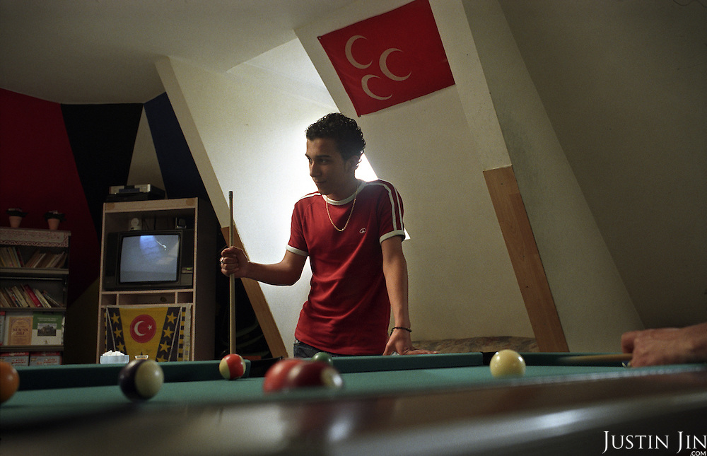 Dutch-Turkish teenager Hakan Dinc plays pool in front of a Turkish flag at a mosque in Amsterdam. .Dinc, 16, was born in the Netherlands. His grandparents from his father?s side came from Turkey in 1971, and his mother came in 1987. Dinc feels more Turkish than Dutch, most of his friends are Turkish and he wants to marry a Turkish girl. During his time off he works in his uncle?s grocery store. Later, he wants to have his own shop. Dinc is following a Commerce course at a vocational school in Amsterdam. .Dinc likes music, pool and chilling out. He has a fourteen-year-old sister and a brother aged ten months. .Picture shot in Amsterdam in 2004 by Justin Jin. .