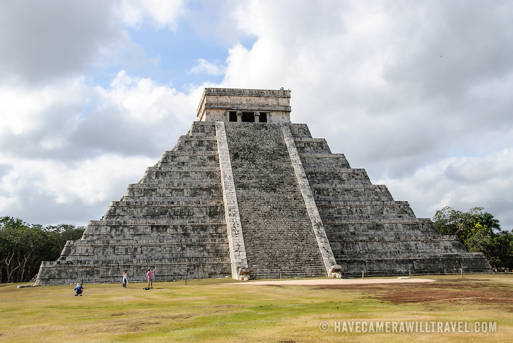 Tourists standing in front of the Temple of Kukulkan (El Castillo) at Chichen Itza Archeological Zone, ruins of a major Maya civilization city in the heart of Mexico's Yucatan Peninsula.