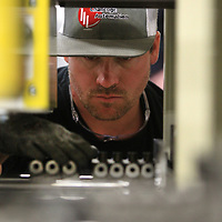 Brett Robbins, an assembly technician at Challenge Automation, places main caps for an engine block into an automated sorting machine for an automotive customer. The machine sorts the different sizes of caps to keep the worker from having to do it by hand and speed up the assembly process.
