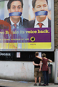 Splashed paint drips down and two voters reading an anti-EU membership 'UK Independence Party's (UKIP) political billboard showing Labour leader Ed Milliband and (coaltion) Deputy PM Nick Clegg - both silent against a bullying European Union, seen in East Dulwich - a relatively affluent district of south London. The ad is displayed before European elections on 22nd May.