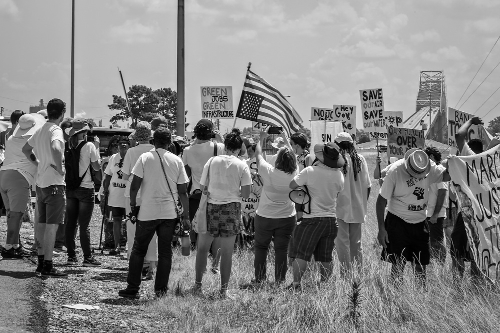 """Marchers  at the approach to the Sunshine Bridge in St. James Louisaina on the third day of a five day march through Louisiana's 'Cancer Alley' held by the Coalition Against Death Alley. The Coalition Against Death Alley (CADA), is a group of Louisiana-based residents and members of various local and state organizations, is calling for a stop to the construction of new petrochemical plants and the passing of stricter regulations on existing industry in the area that include the groups RISE St. James, Justice and Beyond, the Louisiana Bucket Brigade, 350 New Orleans, and the Concerned Citizens of St. John  Louisiana's Cancer Alley, an 80-mile stretch along the Mississippi River, is also known as the """"Petrochemical Corridor,"""" where there are over 100 petrochemical plants and refineries . The Coalition was denied a permit to march over the Sunshine Bridge and the I-10 Bridge."""