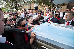© Licensed to London News Pictures. 21/04/2018. Cobham, UK. Paddy Doherty (R) looks on as family members kiss the coffin of Queenie, Elizabeth Doherty at Sacred Heart Church in Cobham, Surrey. Elizabeth Doherty, whose son Paddy Doherty is known for appearing on My Big Fat Gypsy Wedding and winning Celebrity Big Brother 8, died of a heart attack earlier this month. Paddy Doherty claimed his mother has died of a 'broken heart' following the death of her husband almost a year ago. Photo credit: Peter Macdiarmid/LNP