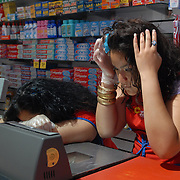 Krystal Leon, 17,  looks at her reflection in the mirror inside the grocery scanner in between customers while bagging groceries during her cashier shift at Steve's C-Town, a grocery store on 9th Street between 5th and 6th Avenues in Park Slope, Brooklyn on June 8, 2007. <br />