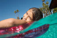 Girl floating in inflatable raft in swimming pool