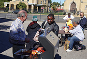 Former Memphis Mayor Dick Hackett  (Left) is the new Executive Director of the Catholic Charities of West Tennessee. Looking to expand their outreach, CCWTN had a cookout in the neighborhood Wednesday.  Hackett serves BBQ hot dogs to the needy.  © Karen Pulfer Focht-
