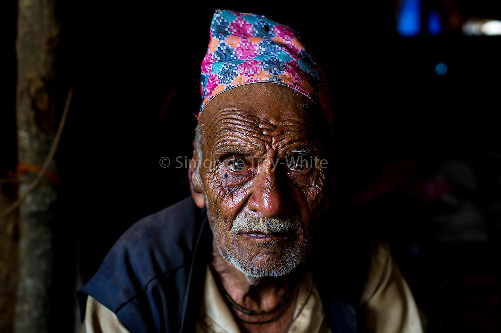 30th April 2015, Sindhupal Chowk District, Nepal. Man Bahadur Bharati (87) in Bharatigaun village, Sindhupal Chowk District, on the 30th April 2015. <br /> He lived through the last major earthquake to hit Nepal 81 years ago in 1934. He was interviewed about the men from the village going overseas to work and said the village had changed for the better in the last 20 yrs, but now everything is at risk again. He said men started leaving to work overseas 10-12 yrs ago. &quot;The fields are barren, but the money is here.&quot; He said it would be good if families could stay together.<br /> <br /> Sindhupalchowk District has seen around 2100 deaths as of 3rd May 2015 which is nearly a third of all fatalities recorded in Nepal from the earthquake with magnitude 7.8 that occurred near Lamjung, Nepal, 50 miles northeast of the capital Kathmandu at 06:11:26 UTC on Apr 25, 2015. The capital has seen considerable devastation including the nine-story Dharahara Tower, one of Kathmandu's landmarks built by Nepal's royal rulers as a watchtower in the 1800s and a UNESCO-recognised historical monument. It was reduced to rubble and there were reports of people trapped. Portions of historic buildings in the World Heritage gazetted site of Patan have also been destroyed as well as many buildings in the old city. <br /> <br /> PHOTOGRAPH BY AND COPYRIGHT OF SIMON DE TREY-WHITE<br /> <br /> + 91 98103 99809<br /> email: simon@simondetreywhite.com<br /> photographer in delhi