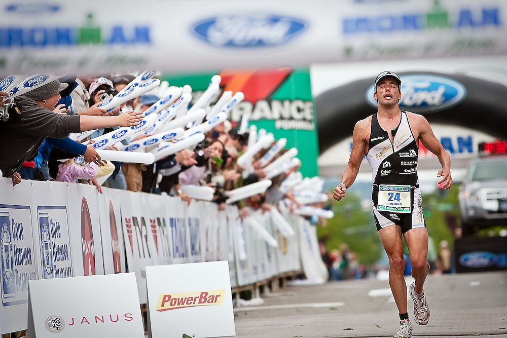 JEROME A. POLLOS/Press..Francisco Pontano, from Spain, pushes through the fatigue as he jogs toward the finish line Sunday to win the Ford Ironman Coeur d'Alene with a time of 8:32:12.