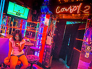 "22 MAY 2014 - BANGKOK, THAILAND: A woman in the Cowboy 2, a bar in the Soi Cowboy ""adult entertainment"" district, checks her smart phone while the TV above her broadcasts the Thai army announcement of a coup replacing the civilian government. The Thai army suspended civilian rule, suspended the constitution and declared the ""military takeover of the nation."" The announcement came just before evening as a meeting between civilian politicians and the army was breaking up with no progress towards resolving the country's political impasse. Civilian politicians were arrested when the meeting ended. The army also declared a curfew from 10PM until 5AM.    PHOTO BY JACK KURTZ"