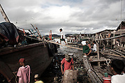 Children playing in the shipyard of their village in southern Myanmar where moken trade fish for supplies like petrol, rice and cooking oil.