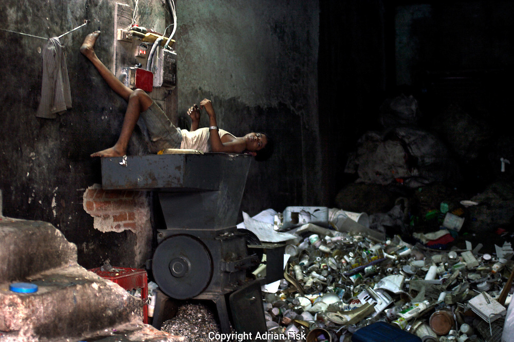 A young lad takes a break from his job of cutting plastic in a room of plastic waste on 21st Oct 2006. Dharavi is the main area in Bombay for recycling.