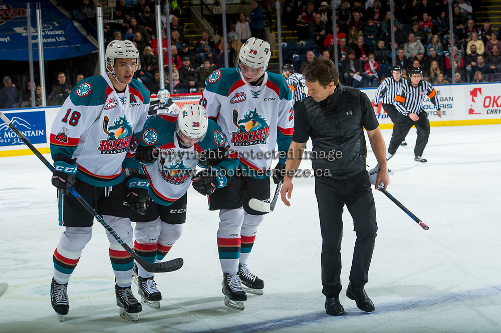 KELOWNA, CANADA - DECEMBER 30: Liam Kindree #26 is assisted off the ice by Carsen Twarynski #18 and Nolan Foote #29 of the Kelowna Rockets with athletic therapist Scott Hoyer against the Victoria Royals on December 30, 2017 at Prospera Place in Kelowna, British Columbia, Canada.  (Photo by Marissa Baecker/Shoot the Breeze)  *** Local Caption ***