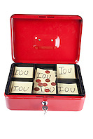 Open box with IOU notes and coins over white background