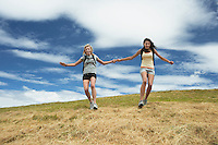Two women holding hands skipping down hill