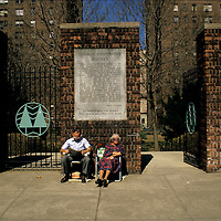 A couple sits at the entrance to the Hillman Cooperative Houses in the Lower East Side of New York City.