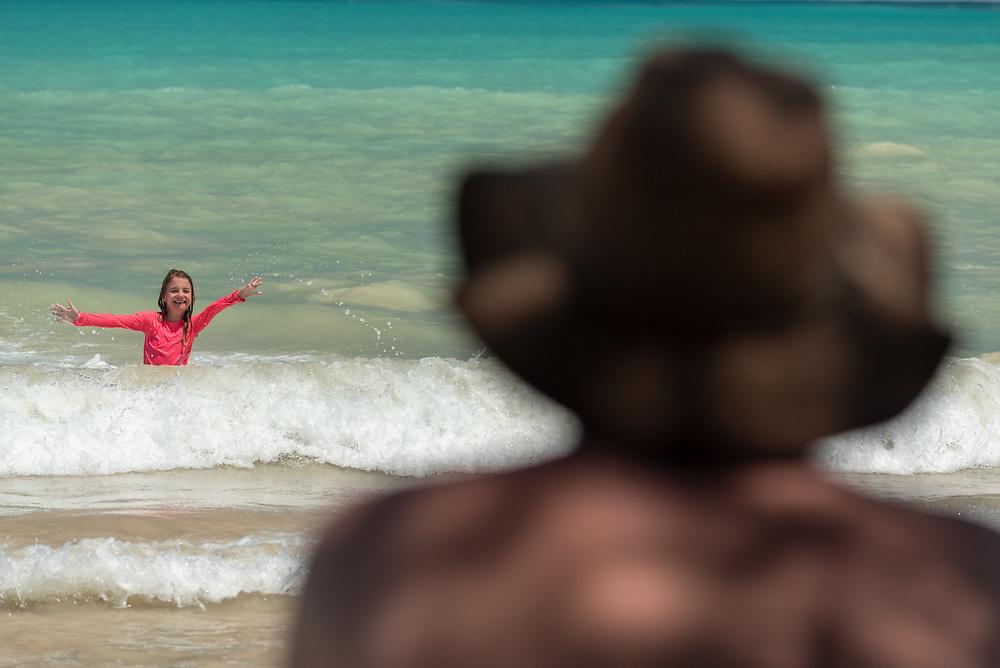 Father watching daughter play in the surf on Garrapatero Beach, Santa Cruz Island, Galapagos Islands, Ecuador.